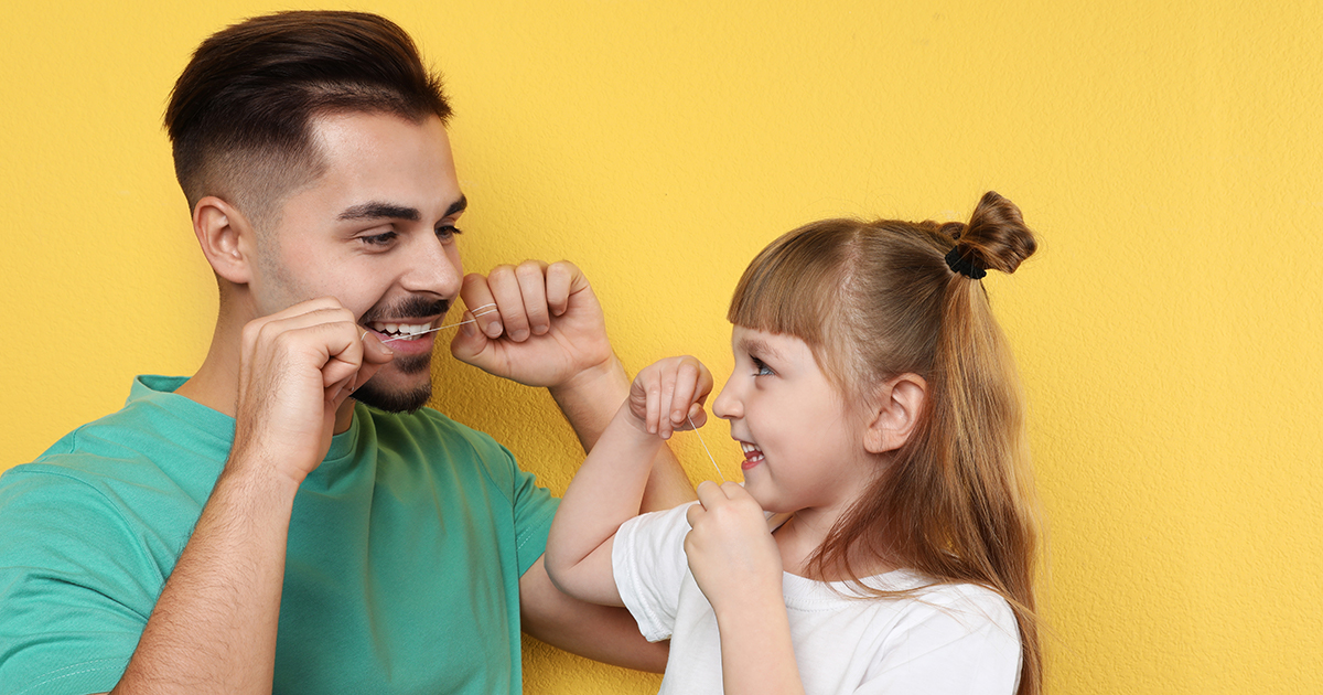 child and dad flossing